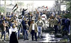 Arabs emerge from the Nusseirat refugee camp during the Palestinian uprising of 1987