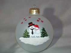 3 1/4 Hand-Painted Glass Ornament. Love is in the air with this hand-painted ornament with little red glittered hearts floating around the snowcouple