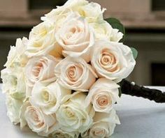 a clutch-style bouquet of cream roses tightly draped in dark ribbon