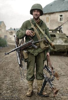 """War Booty,     This photo was on the cover of 'YANK' Magazine, Continental Edition of January 14, 1945, entitled """"PRESENT ARMS"""" it featured Pfc. Robert Leigh and his collection of enemy weapons taken by the 83rd Infantry Division during the Battle of the Hürtgen Forest. (MP.38 and MP.40's, an MG.34 and an MG42). [Colorized by Paul Reynolds]"""