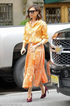 Eye-catching: The fashion designer, 43, caught the eye in a bright tangerine blouse, worn tucked into a coordinating midi skirt
