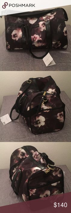 """Adrienne Vittadini Nylon Duffle Bag Maroon/purple floral print. Large main compartment. Inside pocket. Pockets on each end on the outside. Adjustable shoulder strap. Approximate measurements 20"""" long, 11"""" front to back, and 12.5"""" tall. Brand new with tags. Would make an excellent Christmas gift! Adrienne Vittadini Bags Travel Bags"""
