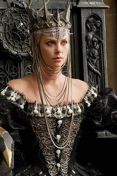 "Stunning costumes with a theme of decay and death were the hallmark for the wardrobe of Queen Ravenna as played by actress Charlize Theron in ""Snow White & the Huntsman"" (2012).  Costume designer Colleen Atwood used various furs, feathers, leathers and pseudo-animalistic fabrics to create the character's creepy couture."