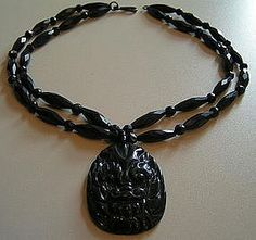 Authentic English Whitby jet beads are faceted; two strands with an incredible poured glass gargoyle pendant. Clasp is typical Victorian enameled metal style. This unusual mourning jewelry possibly refashioned back in the day it wears wonderfully and its quite a conversation piece. Necklace is about 9 each side, pendant drop measures approx 2 1/4. Circa mid 1800s.