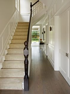 Smoked oak flooring in painted wood panelled hallway showing staircase with bronze stair rods and dark stained handrail.
