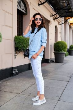 This combination of a light blue denim shirt and white slim jeans is perfect for off-duty occasions. Silver leather slip-on sneakers will contrast beautifully against the rest of the look. Shop this look on Lookastic: https://lookastic.com/women/looks/light-blue-denim-shirt-white-skinny-jeans-silver-slip-on-sneakers/18022 — Light Blue Denim Shirt — Black Leather Crossbody Bag — White Skinny Jeans — Silver Leather Slip-on Sneakers