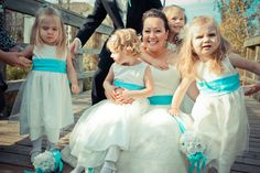 Flowergirls in white dresses with blue waistbands and pomanders