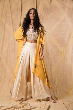 Ivory muga tussar crop top and palazzo pants layered with a mustard muga tussar cape, hand-embroidered with zardozi and thread. indian dress Ivory & Mustard Tussar Cape With Palazzo Indian Attire, Indian Wear, Indian Suits, Indian Gowns Dresses, Pakistani Dresses, Indian Wedding Outfits, Indian Outfits Modern, Indian Weddings, Wedding Dresses