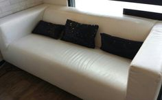 White leather couch with black sequin pillows