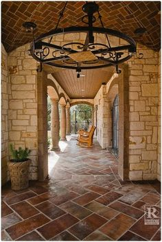 Tile flooring in this breezeway is made up of large format tiles - 12x24 Manganese Saltillo Tile.  Saltillo is also known as Terra Cotta tile.  It comes presealed and is perfect to be used as outdoor tile.  The rustic iron chandelier dresses this space for a completed look.