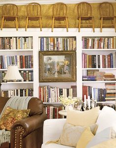 Three bookcases joined with molding provide plenty of space for books and have a built-in feel. The space above the bookcases is put to use storing extra chairs for guests.