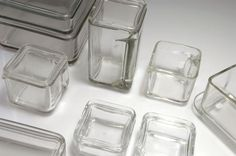 Wilhelm Wagenfeld. 'Kubus' containers, 19 pieces (incl. lids), designed in 1938. Three ewers: H. 9-16.7 cm; five shallow bowls: H. each 5.5 cm; 9.1 x 9.1 cm; 18.1 x 9.1 cm; 18.1 x 18.1 cm; two bowls: H. 8.2 x 18.2 x 9.2 cm; H. 9 x 18.1 x 18.1 cm; small tray: 22.4 x 9.1 cm. Made by Vereinigte Lausitzer Glaswerke, Weisswasser resp. Sendlinger Optische Glaswerke GmbH, Berlin-Zehlendorf. Clear moulded glass. Marked: Maker's marks.