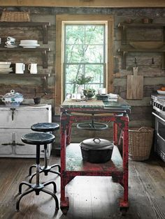 Rustic Retreat  In this Tennessee cabin, an industrial worktable, topped with custom-cut glass, serves as the kitchens island; the stools were also rescued from a factory. A vintage zinc icebox offers hidden storage, while open Douglas-fir shelves hold dishes and cookware. The stainless steel stove is Jenn-Air.