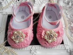 Pink Satin Rosette for baby girls. Made of pink satin fabric with interconnected rosettes. The fasten with velcro on the ankles and are adorned with a tiny matching bow in the front. The bow has a beautiful rhinestone cluster in its center.