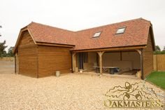 L-shaped oak framed garage with two open bays.