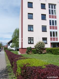 Frisch sanierte Fassade eines Mietshaus mit schönem grünen Garten und Hecke in Hanau am Main