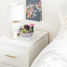 Taking a white Ikea malm and transforming it with marble contact paper and gold handles.