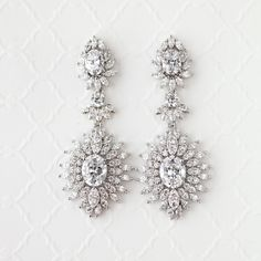 These sophisticated vintage-inspired earrings feature a pendant of a single oval cut CZ surrounded by marquise cut stones and marquise shaped settings. These earrings are for traditional weddings or any formal event. They are 2.25 inches long and 1 inch wide with pierced post backs. AAA grade CZ, rhodium plated and lead free.