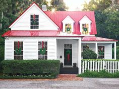 Cottage in Beaufort, South Carolina with a wreaths in each window and red ribbons