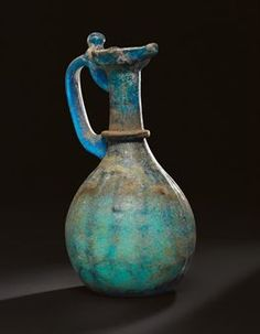 AN UMAYYAD BLUE GLASS EWER  IRAQ OR SYRIA, CIRCA 8TH CENTURY  Rising flat base through moulded rounded body to tubular neck with shaped and pinched spout, the body decorated with groups of three vertical ribs, each side one nipped to join the central vertical one, with applied cobalt-blue handle with an applied ring joining to the back of the spout, fold at top to form a thumb rest, pontil mark, corrosion of the surface, intact  9in. (22.9cm.) high