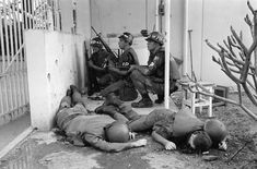 With dead U.S. soldiers in the foreground, U.S. military police take cover behind a wall at the entrance to the U.S. Consulate in Saigon on the first day of the Tet Offensive, January 31, 1968. Viet Cong guerrillas had invaded the grounds of the U.S. embassy compound in the earliest hours of the coordinated Communist offensive. #