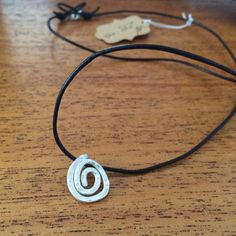 Silver spiral pendant handcrafted from reeling silver. Black leather cord with silver clasps. This makes an excellent gift for both men and women.