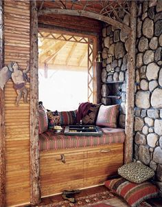 Window seats flank the rock fireplace in the living room. Under them, drawers that hold puzzles and firewood glide on casters and sport handles made from shed deer antlers.