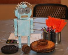 Table-bots - Each table was covered in a silver tablecloth with gears and cogs ordered from Etsy in the center. - Robot Birthday Party #robot #robotparty #centerpiece