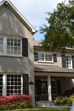 Painted brick home - love these colors with the landscaping. Paint brick taupe and trim white with black shutters???