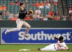 Story Turns a Double Play:   Colorado Rockies shortstop Trevor Story, left, turns a double play over Baltimore Orioles third baseman Manny Machado on July 25, at Camden Yards in Baltimore. The Orioles won 3-2 in 10 innings.