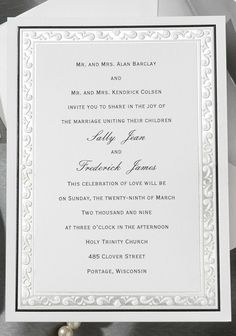 This intricate design is embossed with a classic silver background. A touch of color is added with a black foil stamped border.