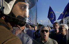 Guardian photographer of the year 2015: Yannis Behrakis | Riot policemen stand between anti-austerity and pro-EU protesters in front of the parliament building during a rally calling on the government to clinch a deal with its international creditors