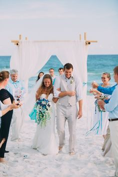 This stunning bamboo beach arbor featured white sheer fabric panels tied back in a curtain style.  The couples accent colors of blues and turquoise are featured in the ribbons and orchids used in the bouquet.  This romantic design was created by Bella Flora 30a.