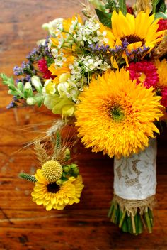 Early Autumn bridal bouquet, Sunflowers, aster, wheat, wax flower, veronica, snap dragon    Groom's Boutonniere, Viking mum, wheat, hypercium berry and veronica