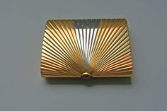 Gold box or cigarette case; four colours of gold (yellow, red, green and white), soldered together to form a sheet and then decorated with ribbed engine-turning to create the sunray pattern. The push-piece to open the box is set with a cabochon ruby. London hallmark 1962; maker's mark. Contained in the original Cartier red leather case with stamped and gilded floral swags, lined inside with pale yellow velvet in the base and cream silk in the lid. The lid printed in gold: CARTIER ...