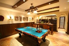 This finished basement has a warm toned tile floor, a pool table and a wet bar in the main entertaining area. What do you think about this basement? Tell us in the comments!
