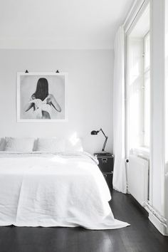This Scandinavian bedroom features a white palette that adds a welcoming atmosph