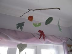 Fabric leaves suspended from a small branch.