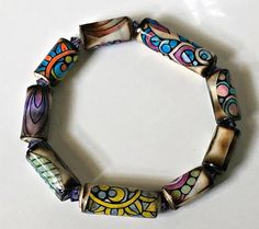 One stretch paper bead bracelet featuring hand colored Zentagle images. I created this gorgeous and super unique Zentanle paper bead bracelet by first rolling various size paper tube beads. I then affixed images from an adult coloring book that were hand colored by me using very high quality colors pencils. These images and beads were then heat manipulated to create great interest and added dimension. The beautiful burnished beads have a faux wood look to them as an end result! The beads are…