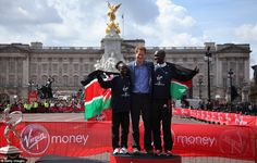 Prince Harry poses with men's professional champion Wilson Kipsang and women's winner Mary Keitany after presenting them with their medals