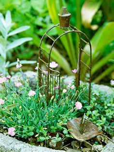 I wonder if I could weld together a little arbor like this.  -- Planted in a stone container, this easy garden features soft pink dianthus and just a couple of accessories. It's part of Pam Vohs' cottage garden in Savannah, Missouri.