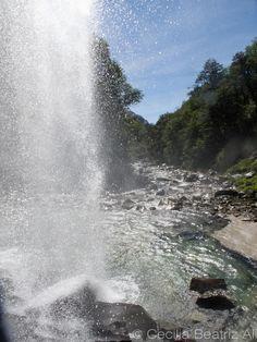 Cascada Dora, Villa La Angostura, provincia de Neuquén, Argentina. Desde la cueva que se da entre la formación rocosa y el velo de la cascada de agua se deja ver el río que pasa por entre las piedras luego de la caída.