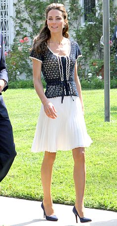 Kate Middleton a navy crocheted top and a white knife-pleated skirt, both from Whistles, navy pumps, an eggshell clutch, sapphire earrings and a delicate diamond cross pendant.