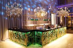 This gorgeous bar is custom built of illuminated malachite panels covered with an intricate gold geometric pattern and finished with dark green leather countertops. #wedding #bar Photography: Bob & Dawn Davis Photography. Read More: https://www.insideweddings.com/weddings/a-dream-winter-wedding-at-the-art-institute-of-chicago/563/