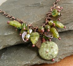 Antiqued copper beaded necklace featuring a cluster of earth toned beads and charms.