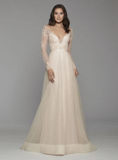 Blush tulle Aline bridal gown, floral beaded and embroidered long sleeve bodice, draped deep V neckline, sweetheart underlay, ribbon at natural waist, sheer high back with covered buttons and chapel train.Alternative Color: Ivory/Ivory