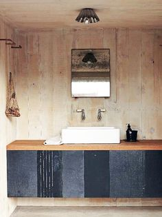Rustic yet totally polished look for this bathroom with a limed oak wall and custom black cabinets with a wood countertop.