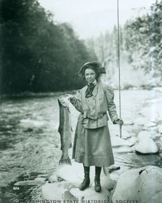 Eleanor Chittenden, daughter of Brigadier General Hiram Chittenden, holds a steelhead trout on the Elwha River during an outing of the Mountaineers. Taken August 1, 1907, by Curtis Asahel.