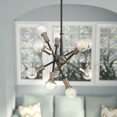 Industrial-chic style meets contemporary design in this 10-light sputnik chandelier. Made with a metal frame, this distinctive design showcases a simple circular canopy, a straight down rod, and ten lights jutting out from a small spherical center like a starburst explosion. Establish a hip, contemporary aesthetic in your open concept living room by rolling out a vibrant overdyed ornate area rug to define the space, then set a reclaimed wood end table with iron hairpin legs between a…