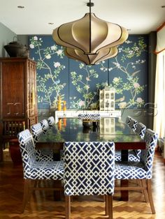 Oriental panels in dining room with upholstered chairs in London townhouse apartment  UK